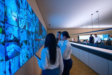 Security guards standing in front of a large CCTV monitor at the main control room while reading and discussing plans