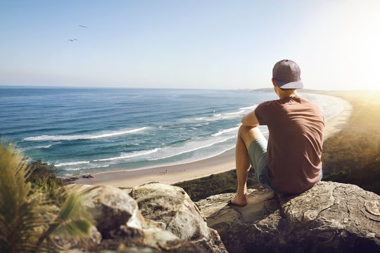 Young man sitting on a rock above a beautiful coastline