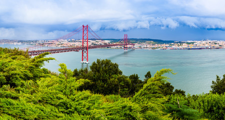 Landscape of Lisbon, Portugal skyline and the 25th of April bridge over the Tagus river estuary as...