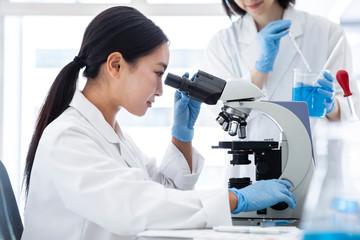 顕微鏡を覗き込む女性研究員