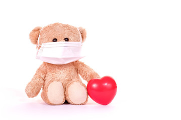 Teddy bear and red heart is wearing a PM 2.5 pollution masks and protect virus on white background. Health care concept.