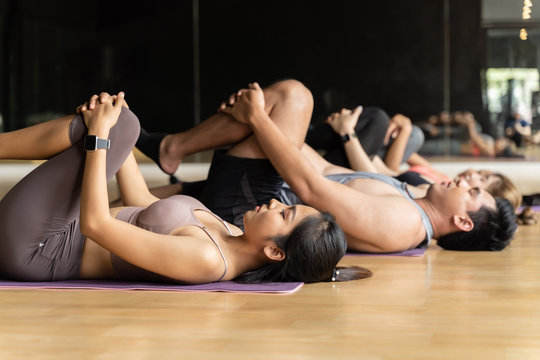 Group of Asian women and man doing pilates lying on yoga mats in aerobics class. Young sporty people stretching legs on the floor in gym studio. Fitness and bodycare concept