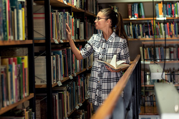 Female librarian works in the library organizing book on bookshelf.