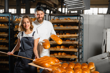 Keuken foto achterwand Bakkerij Young bakers with a wooden shovel with bread in their hands against the background of shelving with bread in a bakery. Industrial bread production