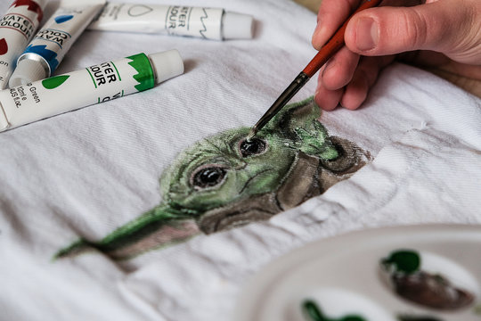 Baby Yoda drawing on fabric with acrylic paints. Baby Yoda popular character from Star Wars films and Mandalorian TV series Lucasfilm fan art. Kropivnitskiy, Ukraine, January 7, 2020