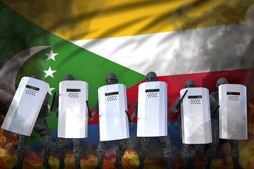Comoros protest fighting concept, police guards in heavy smoke and fire protecting order against riot - military 3D Illustration on flag background