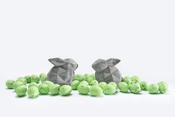 Zwei Osterhasen zwischen grünen Ostereiern