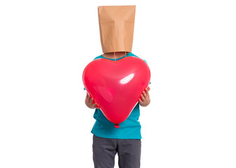 Poster - Valentines Day concept. Teen boy with paper bag over his head holds heart shaped balloon, isolated on white background. Boy holding symbol of love, family, hope. Teenager cover head with bag.