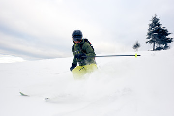 Skier male into deep white snow powder on snow-covered high mountain peak. Extreme skiing in winter sports season. Dangerous, activity, thrill concept. Grey sky and pine tree on background. Front view