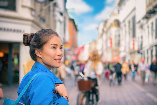 Tourist chinese young woman walking in city street shopping on travel vacation in fall autumn spring happy. Copenhagen city, Denmark.