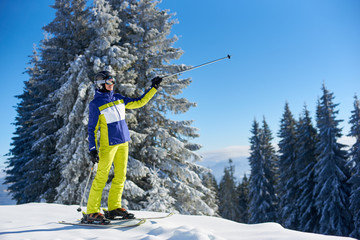 Rejoicing female skier before skiing from downhill. Smiling woman in goggles showing with ski poles something far away. Picturesque snowy fir trees on blue sky background. Active recreation concept.