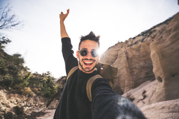 Happy smiling man takes a selfie at vacation on a mountain