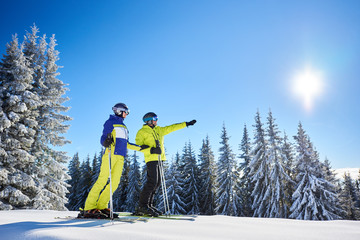 Low angle shot of skiers resting during skiing in sunny winter weather. Male skier showing sun high in blue sky over winter mountains. Fantastic recreational area of ski resort on background.
