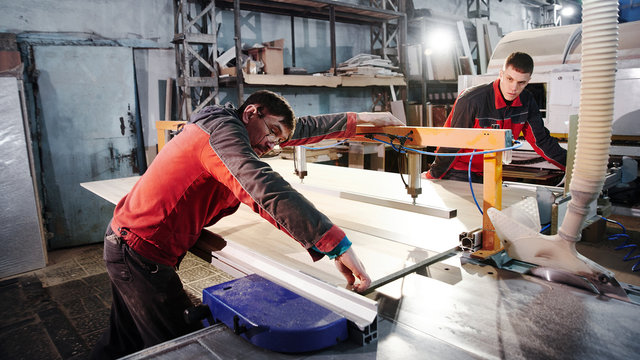 Process of production and manufacture of wooden furniture in furniture factory. Worker carpenter man in overalls processes wood on special equipment