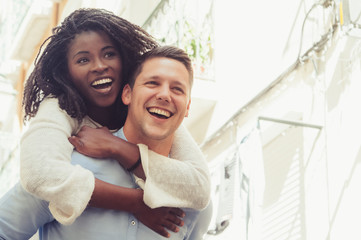 Young man laughing and carrying girlfriend on back outdoors. Happy interracial couple in street. Romance and happiness concept. Front view.
