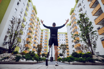 Fotomurales - Rear view of handsome sportsman with artificial leg standing with hands in the air outdoors surrounded by buildings.