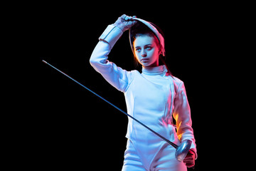 Ready. Teen girl in fencing costume with sword in hand isolated on black background, neon light. Young model practicing and training in motion, action. Copyspace. Sport, youth, healthy lifestyle.