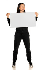 Young smiling woman in black track suit holding empty white board