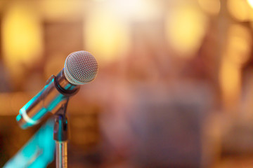 Close up of high fidelity microphone setting on stand with colorful abstract light bokeh background...