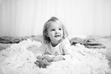Little cute girl lying on bed and look around. Black and white picture. Small child is playing with toy.