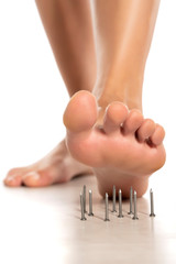 a woman's foot stepped on nails