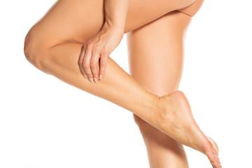 woman massaging her painful leg on white