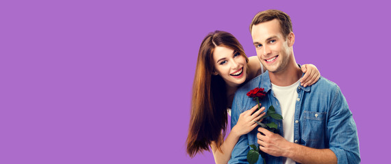 Love, relationship, dating, flirting, romantic concept - portrait picture of happy couple with flower, looking at camera. Purple violet color background. Copy space for some text.