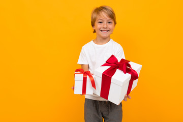 Caucasian boy holds many white boxes with gifts and rejoices, portrait isolated on yellow background