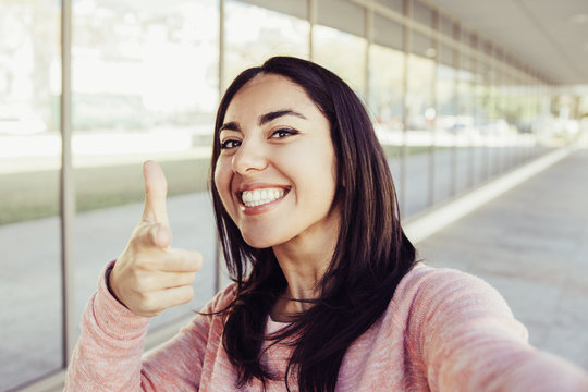 Smiling woman taking selfie photo and pointing at you outdoors. Pretty young lady looking at camera with building wall and walkway in background. Selfie and tourism concept. Front view.