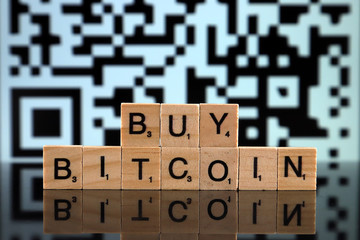 WROCLAW, POLAND - FEBRUARY 04, 2020: Words BUY BITCOIN made of small wooden letters. Conceptual image for investors wanting to buy bitcoins or other cryptocurrencies.