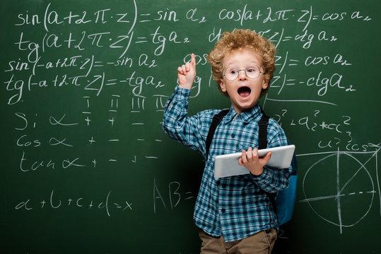 smart kid in glasses having idea while holding digital tablet near chalkboard