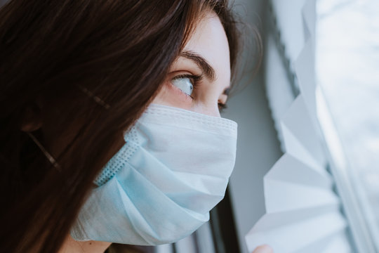 Young female in a medical protective mask looks out the window. Coronovirus Quarantine Concept