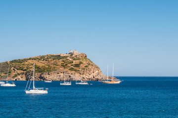 Many sailing boats and yachts docked at the bay of cape sounio with the ancient temple of Poseidon in the background