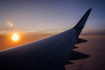 Flying above the clouds. Scenic view of sun, cloudy sky and airplane wing at sunset.
