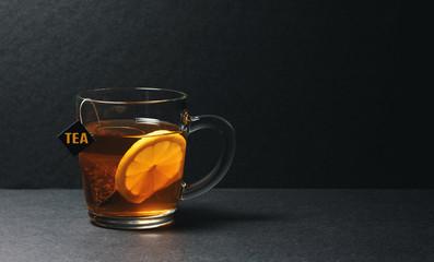 glass of a black tea bag with lemon