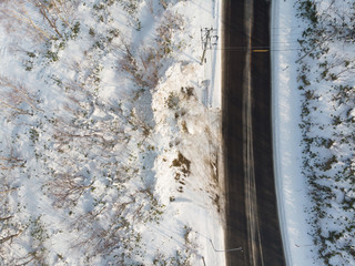 Vertical view from height of a road among snow covered ground, a sense of adventure among nature