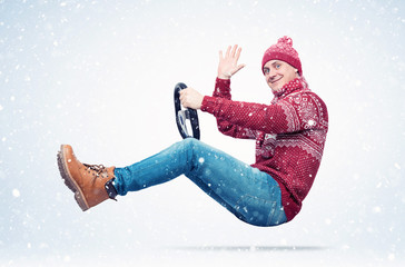 Happy smiling man in a red sweater, hat and scarf drives a car sends greetings to the camera, in snow. Auto driver concept