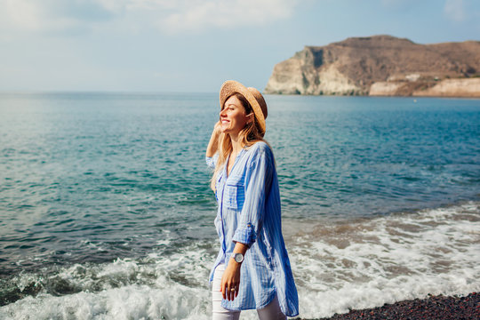 Traveler woman walking along shore of Red beach on Santorini island, Greece. Traveling and vacation concept