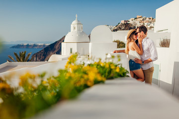 Santorini, Greece honeymoon. Couple in love walking and kissing in Fira. Husband and wife enjoying sea landscape. Fototapete