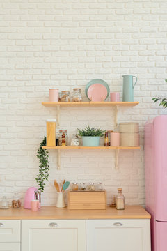 Kitchen shelves, wooden surface and pink fridge on white background. White kitchen interior counter top