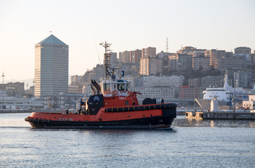 GENOA, ITALY, JANUARY 23, 2020 - A tugboat in the port of Genoa, Italy,  with modern buildings on the background.