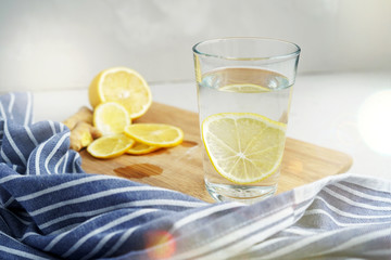Refreshing drink with lemon on a gray background. Warm water with a slice of lemon next to a blue napkin