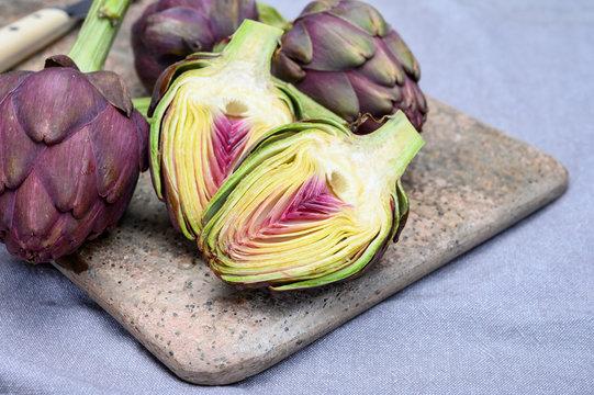 Heads of raw fresh purple artichoke plant ready to cook