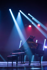 the piano on stage in the spotlight.