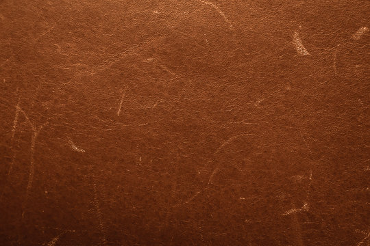 Old brown scratched leathers leather. Vintage leather texture, damaged surface, grunge backdrop. Shabby weathered material.