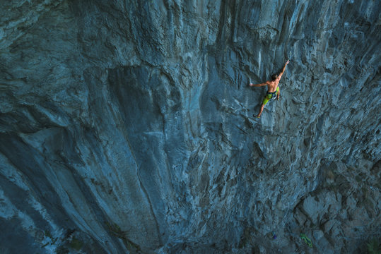 Powerful sportive rock climber climbing