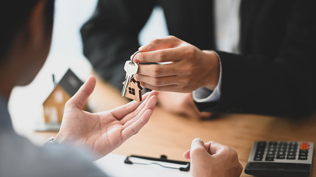 Cropped shot of House broker giving a property key to his customer while he has writing/signing on agreement at the modern wooden desk. Loan, Debt, Credit, Buying or Selling agreement concept.