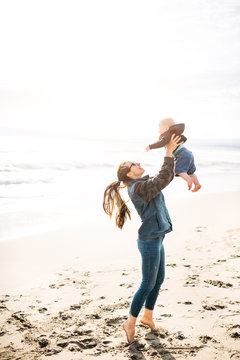 Happy family. mom holds her baby boy on the beach