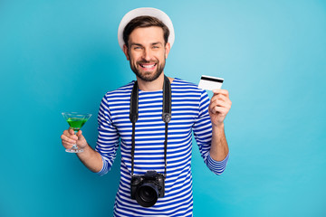 I'll pay. Photo of attractive guy photographer hold digital camera traveler buy credit card green cocktail wear striped sailor shirt vest cap isolated blue color background
