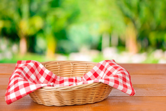 Basket with red checkered cloth inside on a wooden table